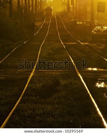 Tram on sunset, diagonal of rails - stock photo