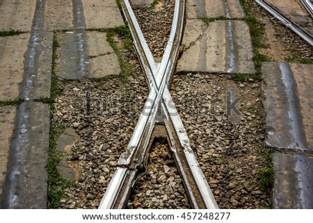 Tram track welded crossing pieces against green grass and concrete plates