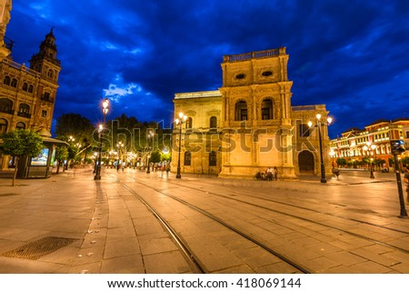 Tram tracks, historic buildings and the streets of the center of Seville illuminated by night. Seville town, Andalusia, Spain. - stock photo