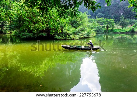 TRANG AN ECO-TOURISM SITE, NINHBINH, VIETNAM - NOVEMBER 2, 2014 - An unidentified woman sailing a boat on a waterway. This location is very famous for beautiful landscape. It's a UNESCO heritage site. - stock photo