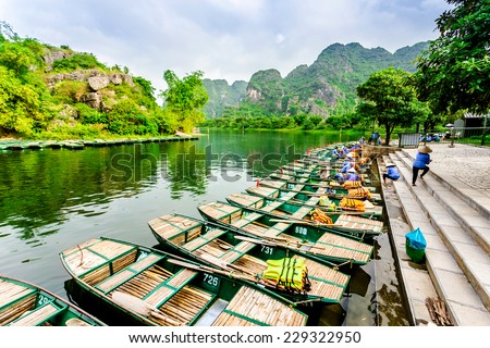TRANG AN ECO-TOURISM SITE, NINHBINH, VIETNAM - NOVEMBER 2, 2014 - Boats waiting for their turns to serve tourists at wharf. This location is very famous and has become a UNESCO heritage site. - stock photo