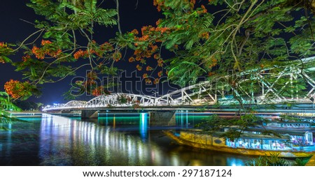 Trang Tien Bridge lit up at night reflected underwater beside sparkling colors are flamboyant flowering stems in summer weather, beneath the boat leaving dock carrying travelers. - stock photo