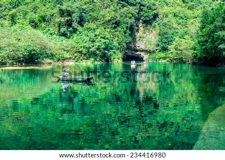TRANGAN ECO-TOURIST COMPLEX, VIETNAM - NOVEMBER 27, 2014 - An unidentified woman sailing a boat on the stream full of seaweed alga. The Complex a UNESCO site & very famous for its natural beauty. - stock photo
