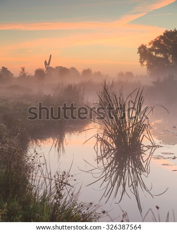 Tranquil and foggy sunrise in the Dutch countryside near a windmill. Groningen, Netherlands - stock photo