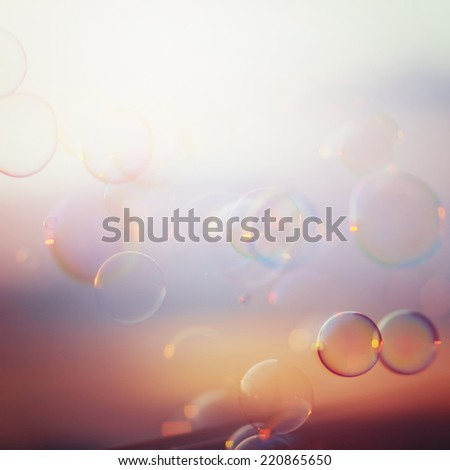 Tranquil background with bubbles floating in the sunset. Image toned in vintage instagram colors. Square composition. - stock photo