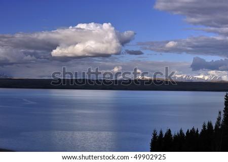 Tranquil, calm Lake Pukaki mirrors tufts of white clouds New Zealand - stock photo