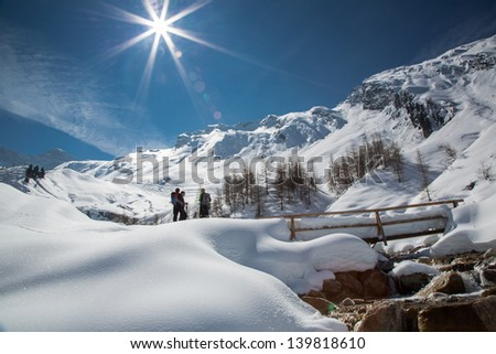 Tranquil early spring scene in the mountains with small group of people standing by snow covered bridge and flowing stream under magnificent snow covered mountain peaks and glaciers of the Alps. - stock photo