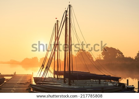 Tranquil, foggy sunrise at a pier with sailing boats. - stock photo