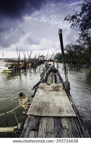 tranquil image at wooden jetty with dark clouds. fisherman boat anchored at the jetty. - stock photo