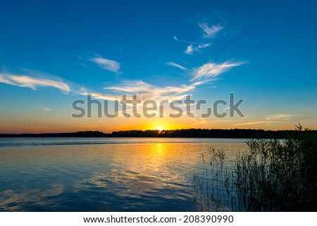 tranquil lake and the setting sun over the horizon - stock photo