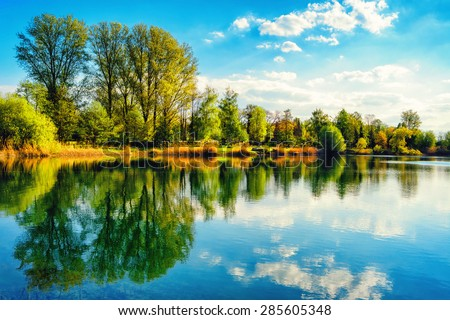 Tranquil landscape at a lake, with the vibrant sky, white clouds and the trees reflected symmetrically in the clean blue water - stock photo