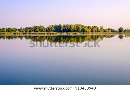 Tranquil lush green tropical island at sunset against a glowing colorful sky mirrored on the surface of the still water below - stock photo