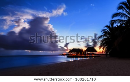 Tranquil night over beach resort, exotic nature of Maldives, scenic destination, luxury bungalow and restaurant on seashore - stock photo