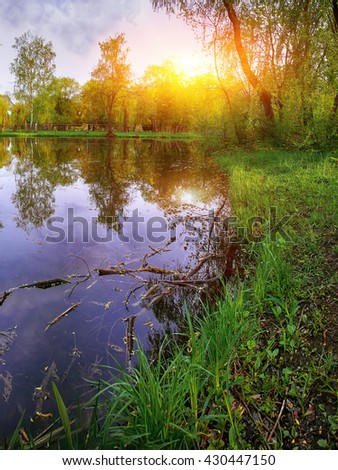 Tranquil Pond With Lush Green Woodland Park in Sunshine. Reflection of trees in water - stock photo
