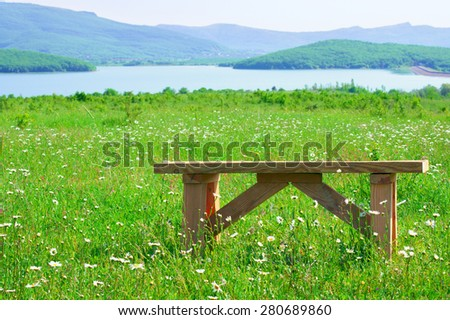 Tranquil rural landscape: spring meadow with daisy and rustic wood bench against lake and mountains. Focus on bench and foreground. - stock photo