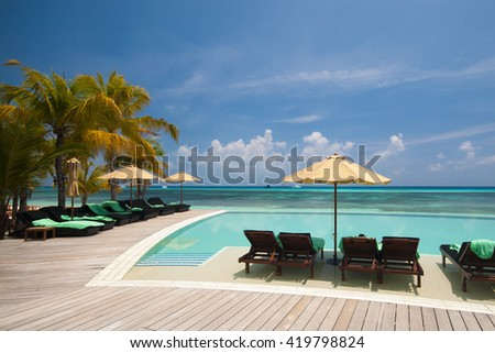 Tranquil scene of a swimming pool and beach with palm trees and white sand. Infinity Pool.  - stock photo
