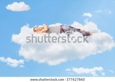 Tranquil scene of a young woman dreaming and sleeping on a cloud up in the sky - stock photo
