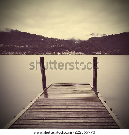 Tranquil scene of old wooden pier and misty Italian Alps mountains on background. Pella town view from Isola San Giulio  on Lago d'Orta - stock photo