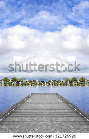 Tranquil scene. Pier in the village Zaanse Schans. Picturesque view of a Dutch village located at the river. - stock photo