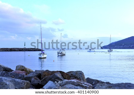 Tranquil sea scene with lighthouse and anchored boats after the sunset. - stock photo