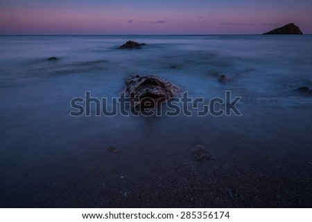 Tranquil seascape with water motion and rock island - stock photo