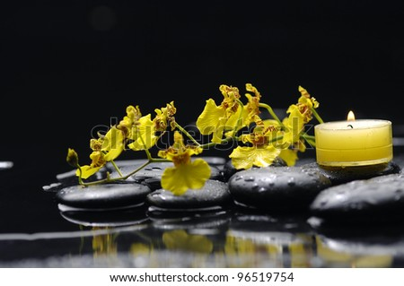 tranquil spa scene -burning candle and yellow orchid on pebbles