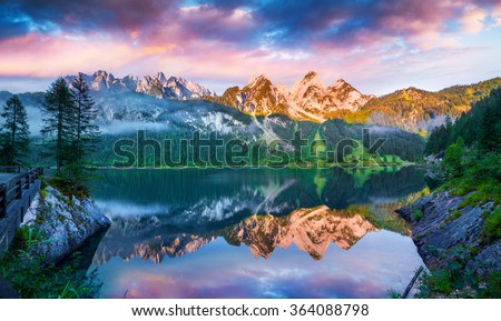 Tranquil summer scene on the Vorderer Gosausee lake in the Austrian Alps. Colorful sky reflected from mirror surface of lake. Austria, Europe. - stock photo