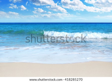 Tranquil sun and sea scene with rolling waves and white sand. - stock photo