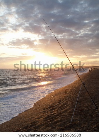 Tranquil sun setting on horizon over ocean with fishing rod in foreground