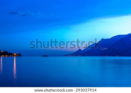 Tranquil sunset and evening illuminations of the beautiful town of Malcesine on Lake Garda in Italy. - stock photo
