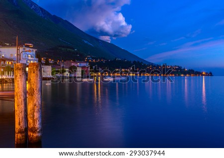Tranquil sunset and evening illuminations of the beautiful town of Malcesine on Lake Garda in Italy.