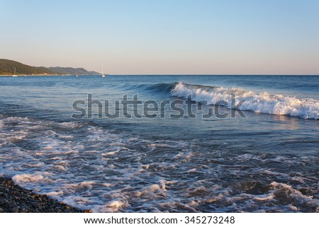 Tranquil surf on the beach against the backdrop of the mountainous coast - stock photo