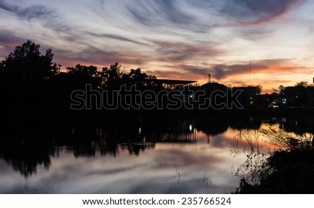Tranquil urban scene with dramatic sky over the pond - stock photo