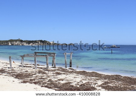 Tranquil view  of the isolated seaweed covered   beach with wooden poles of old jetty  and  Indian Ocean at remote  Hamelin Bay  a popular fishing location in South Western Australia in early summer . - stock photo
