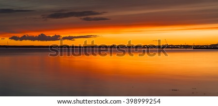 Tranquil waters and orange sun glow over still seas - stock photo