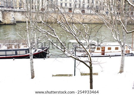 Tranquil winter scene in Paris : covered with snow river side of the Seine river with it's boats and parisian buildings visible on the other side.  - stock photo