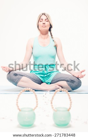 Tranquil young woman sitting cross-legged on a mat on the floor practicing yoga and meditating with her eyes closed in a turquoise outfit with matching blue glass containers in front of her - stock photo