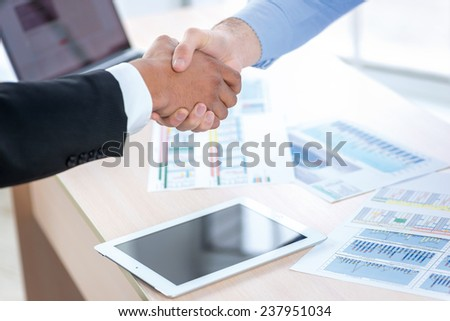 Transaction occurred. Close-up view of a handshake while two successful businessman shaking hands at the table against each in the business office in formal wear and work at a laptop.