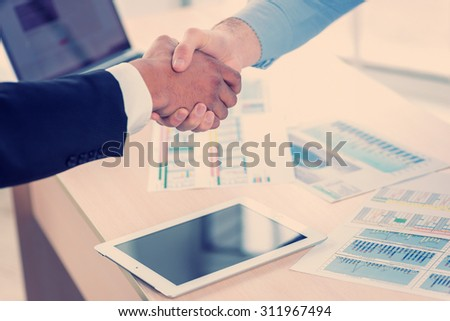 Transaction occurred. Close-up view of a handshake while two successful businessman shaking hands at the table against each in the business office in formal wear and work at a laptop. - stock photo