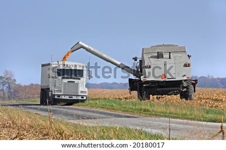 Transferring corn from a combine into a truck - stock photo