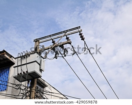 Transformer and power lines on electric pole on high power station in city - stock photo