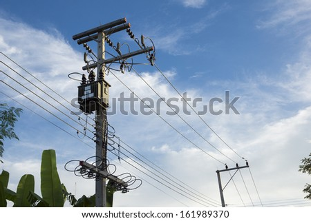 Transformers of an electrical post with power lines - stock photo