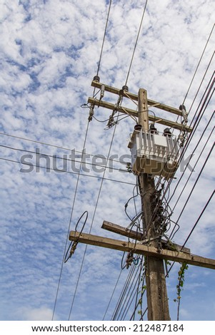 transformers of an electrical post with power-lines against brig - stock photo