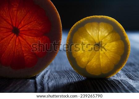 Translucent cut of a ripe citrus (grapefruit and lemon (slice). Close-up. Macro. Soft focus. - stock photo
