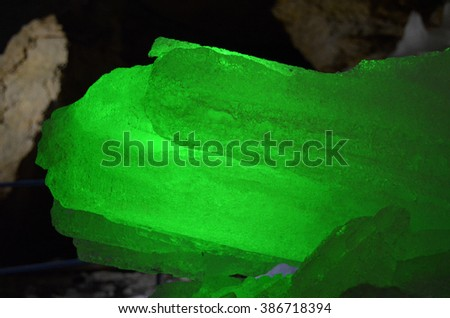 Translucent ice crystal illuminated from behind by verdant light. A natural false-crystal of ice grown in cold cave