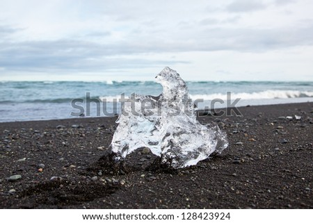 Translucent piece of ice on a black lava beach in Iceland - stock photo