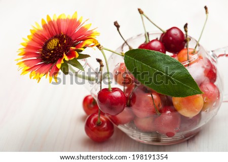 Translucent pot of red and yellow cherries on white wooden background - stock photo