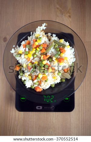 Translucent white plate with rice and vegetables is at home kitchen electronics scales to count calories in food on wooden table. Top view vertical photo closeup - stock photo