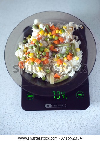 Translucent white plate with rice and vegetables is at home kitchen electronics scales to count calories in food. Top view photo closeup - stock photo
