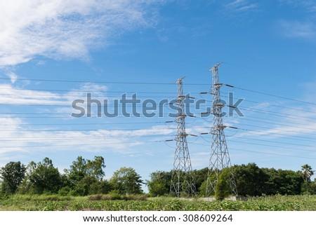 transmission High voltage electricity pylon with blue sky background - stock photo